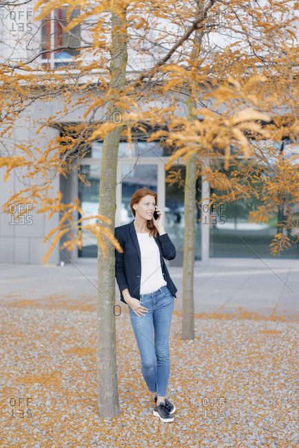 Smiling businesswoman on cell phone outdoors in the city in autumn