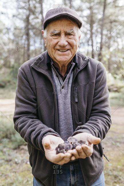 Portrait of smiling senior man showing found mushrooms