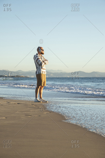 Man with headphones and sunglasses at the beach