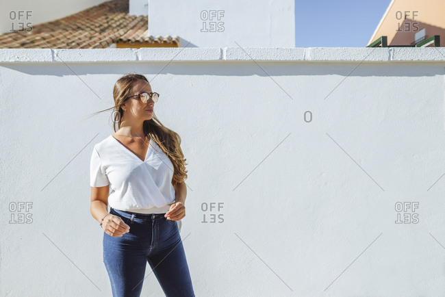 Woman with sunglasses standing in front of white wall