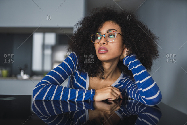 Portrait of daydreaming young woman at home