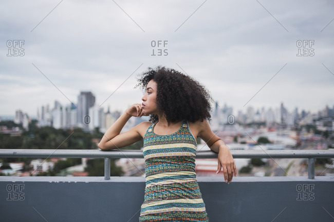 Panama- Panama City- pensive young woman on balcony looking at distance