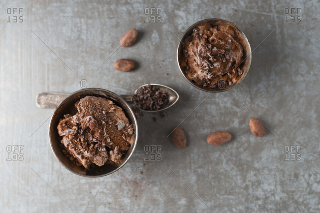 Cups of chocolate ice cream sprinkled with cacao and cacao nibs