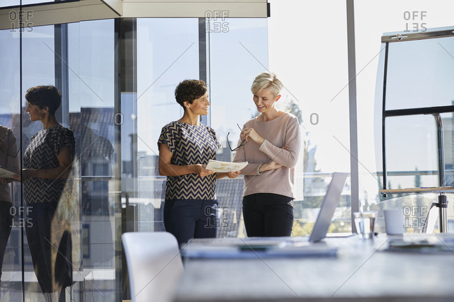 Two smiling businesswomen discussing document at the window in office