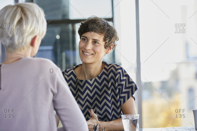 Two businesswomen talking at desk in office
