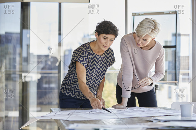 Two businesswomen discussing floor plan on desk in office