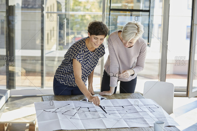Two smiling businesswomen discussing floor plan on desk in office