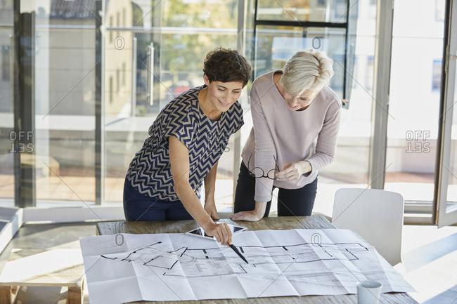 Two smiling businesswomen discussing floor plan on desk in office