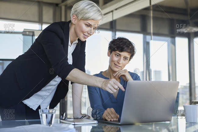 Two smiling businesswomen sharing laptop at desk in office