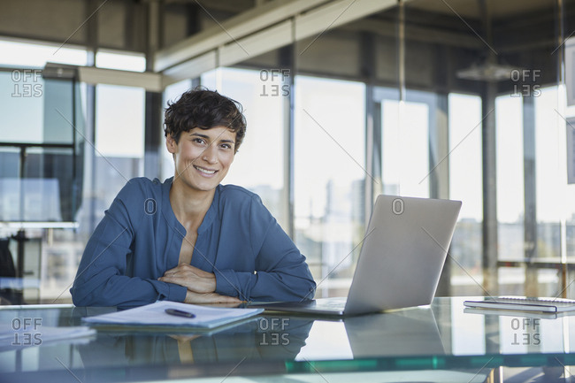 Portrait of confident businesswoman sitting at desk in office with laptop
