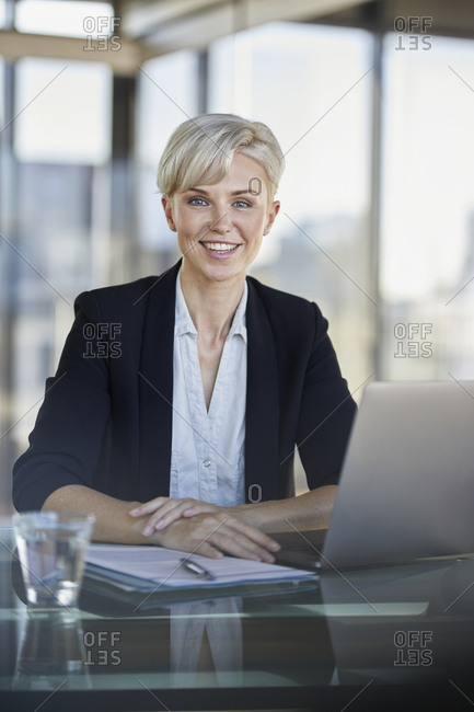 Portrait of smiling businesswoman sitting at desk in office with laptop