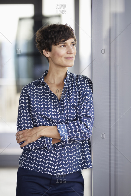 Smiling businesswoman in office looking out of window