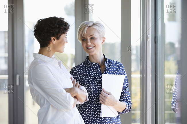 Two smiling businesswomen talking at the window in office
