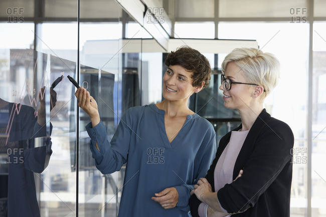Two smiling businesswomen looking at chart on glass pane in office
