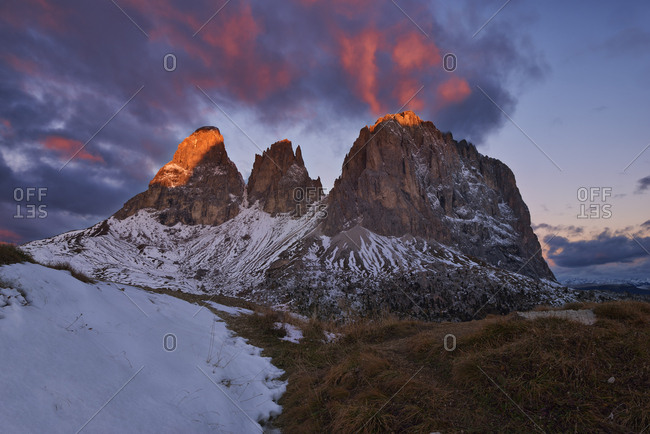 Italy- Alto Adige- Dolomites- Sassolungo- Fuenffingerspitze and Grohmannspitze at sunrise twilight- late autumn with first snow