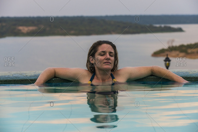 Africa- Uganda- Queen Elizabeth National Park- Woman relaxing in a pool above Kazinga channel
