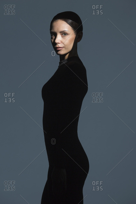 Portrait of slim woman dressed in black with flare on her face