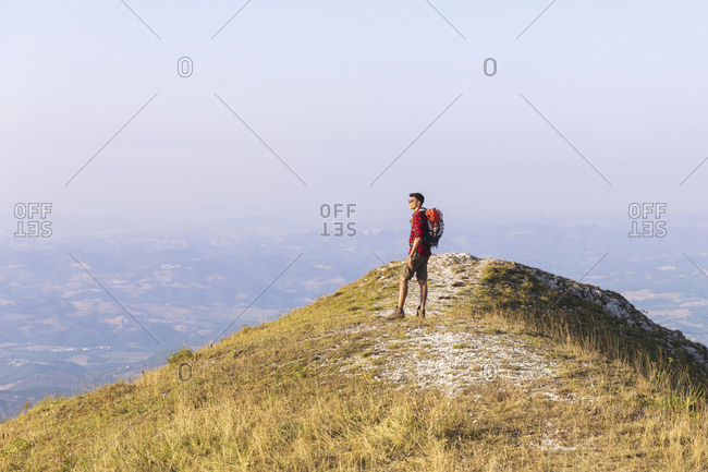 Italy- Monte Nerone- hiker on top of a mountain looking at panorama