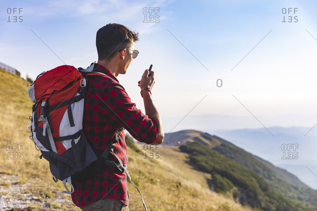 Italy- Monte Nerone- hiker on top of a mountain talking on a walkie talkie