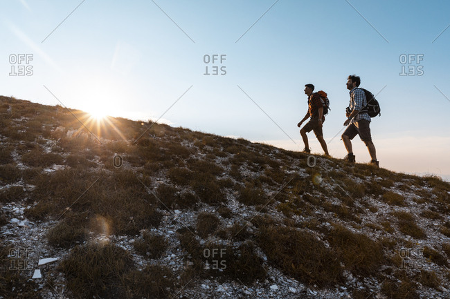 Italy- Monte Nerone- two men hiking in mountains at sunset