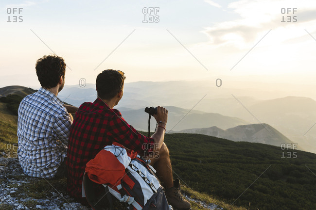 Italy- Monte Nerone- two hikers on top of a mountain enjoying the view at sunset