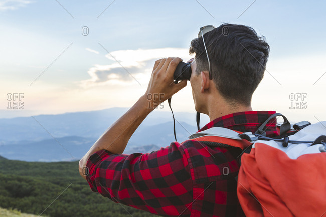 Italy- Monte Nerone- hiker in the mountains looking with binocular