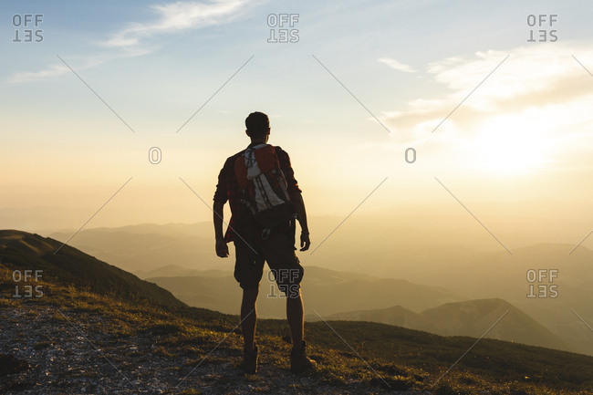 Italy- Monte Nerone- hiker on top of a mountain looking at panorama at sunset