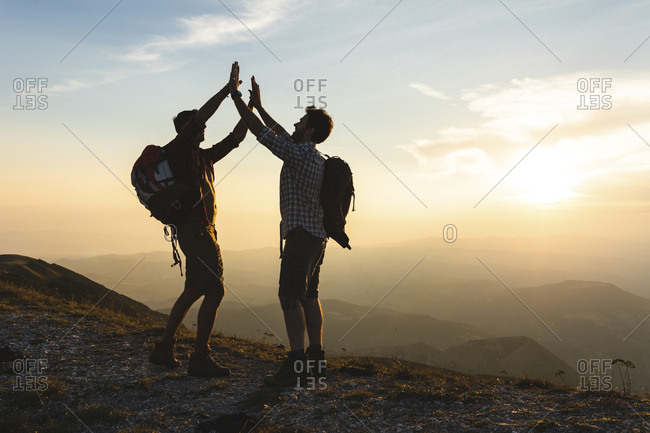 Italy- Monte Nerone- two happy and successful hikers in the mountains at sunset