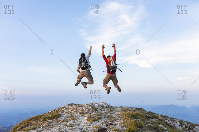 Italy- Monte Nerone- two happy and successful hikers jumping on top of a mountain