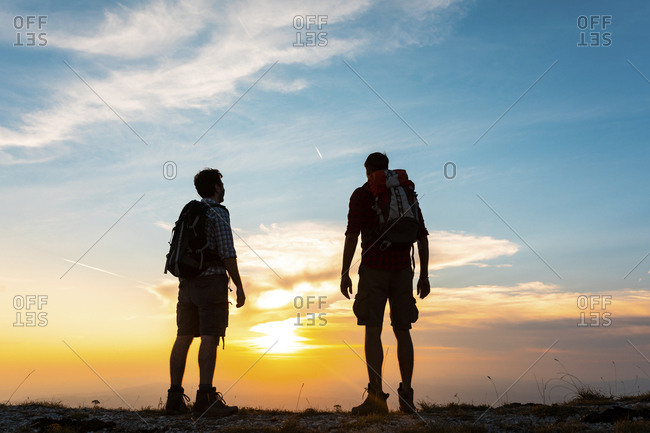 Italy- Monte Nerone- two hikers enjoying the view on top of a mountain at sunset