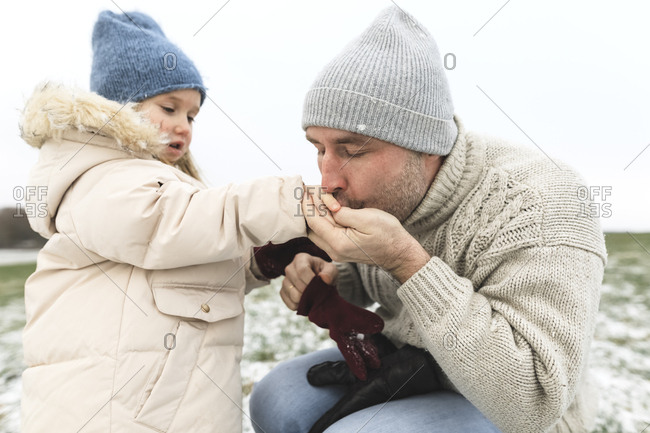 Father warming cold hands of daughter in winter