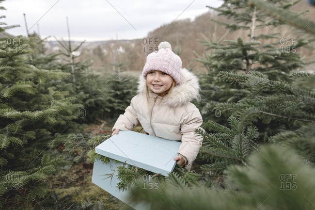 Happy girl carrying gift box on a Christmas tree plantation