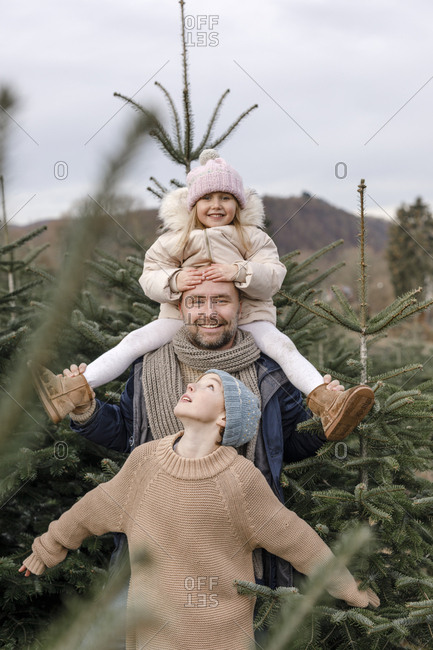 Portrait of happy father with two children on a Christmas tree plantation