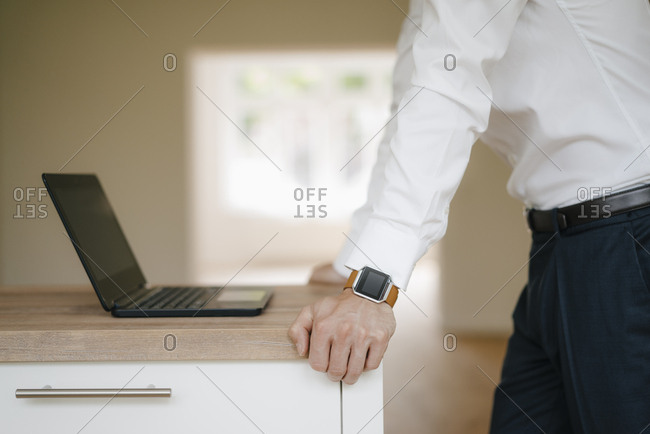 Businessman in leaning on kitchen surface- using laptop- wearing smart watch