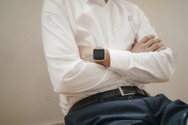 Mid section of a businessman wearing smart watch with arms crossed