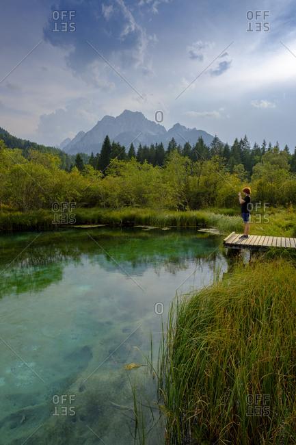 Slovenia- Gorenjska- near Ratece- Sava Dolinka- source- Lake Zelenci- young man standing on jetty