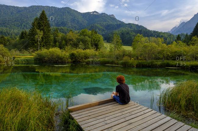 Slovenia- Gorenjska- near Ratece- Sava Dolinka- source- Lake Zelenci- young man sitting on jetty