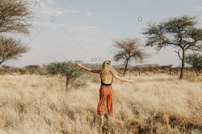 Africa- Namibia- blonde woman in grassland