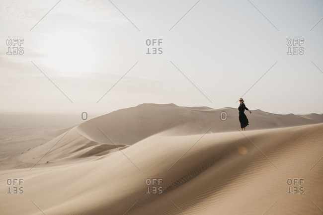 Namibia- Namib- black dressed woman standing on desert dune