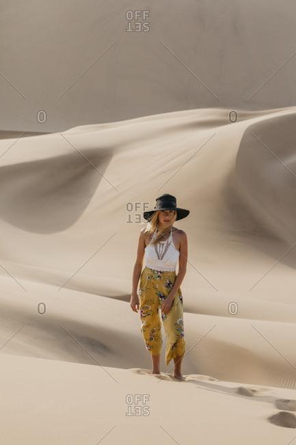 Namibia- Namib- fashionable young woman standing on desert dune