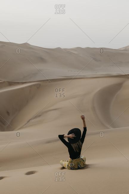 Namibia- Namib- back view of fashionable woman sitting on desert dune