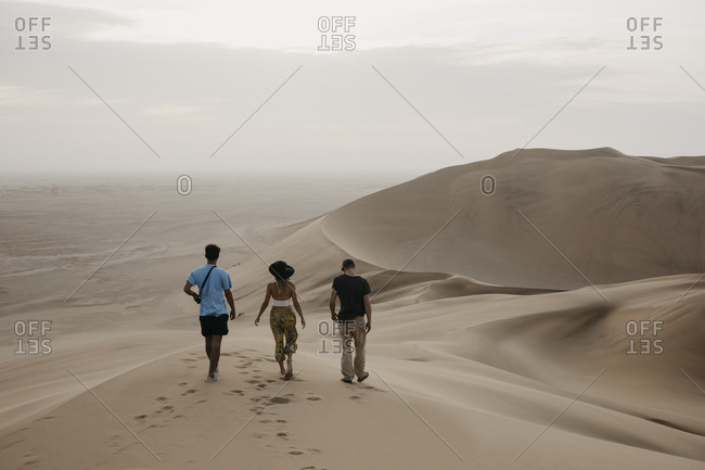 Namibia- Namib- back view of three friends walking side by side on desert dune