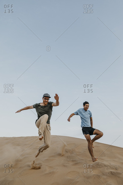 Namibia- Namib- two friends jumping down desert dune