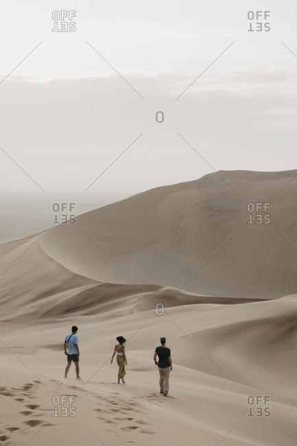 Namibia- Namib- three friends walking down desert dune