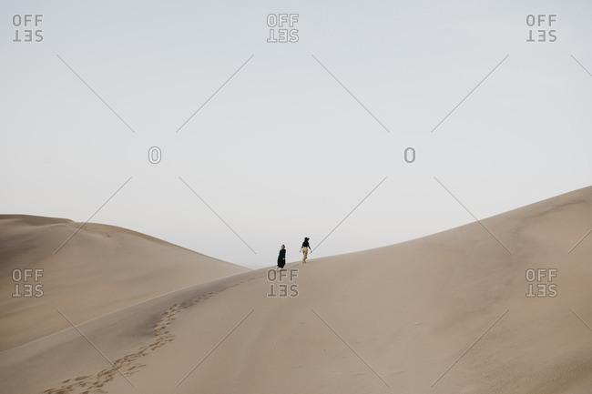 Namibia- Namib- back view of two women walking on desert dune