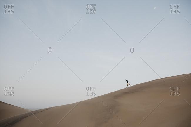 Namibia- Namib- woman running down desert dune