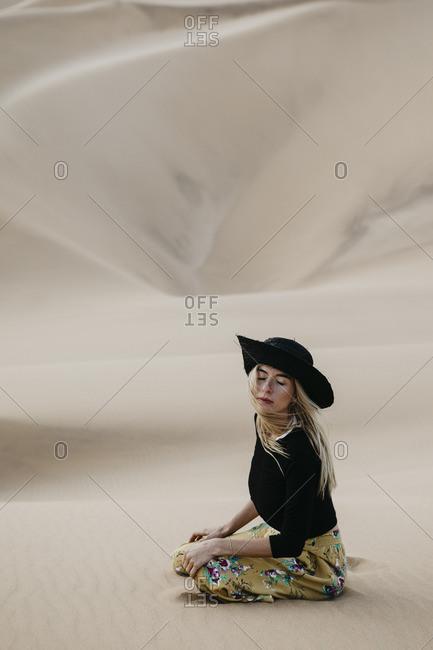 Namibia- Namib- portrait of fashionable woman sitting on desert dune