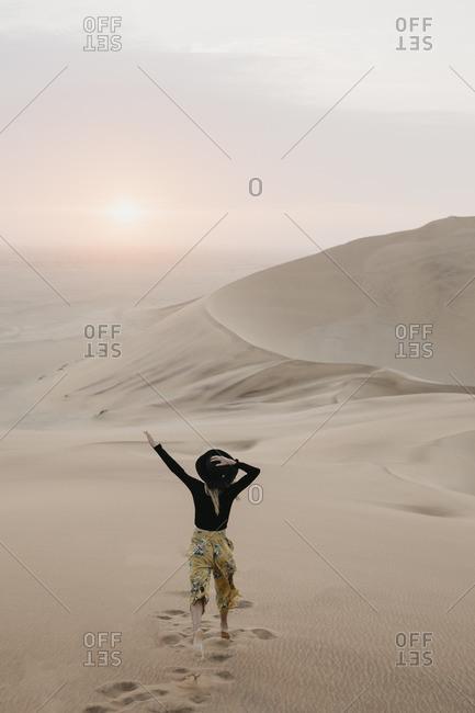 Namibia- Namib- back view of fashionable woman jumping on desert dune