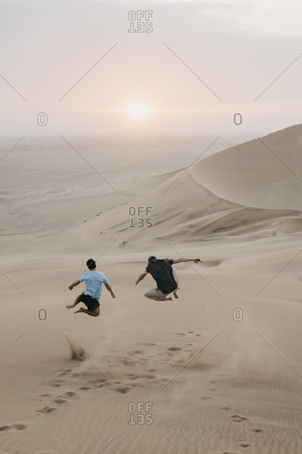 Namibia- Namib- back view of two friends jumping in the air on desert dune