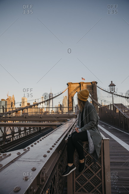 USA- New York- New York City- female tourist sitting on Brooklyn Bridge in the morning light